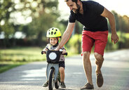 Father teaching little son riding bicycle - HAPF02736