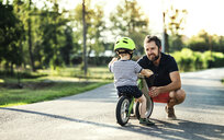 Father supporting little son on bike - HAPF02739
