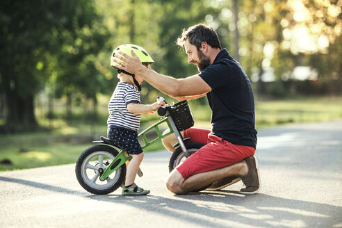 Father supporting little son on bike - HAPF02742