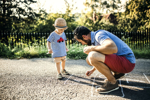 Father drawing Hopscotch on asphalt while his little son watching him - HAPF02745