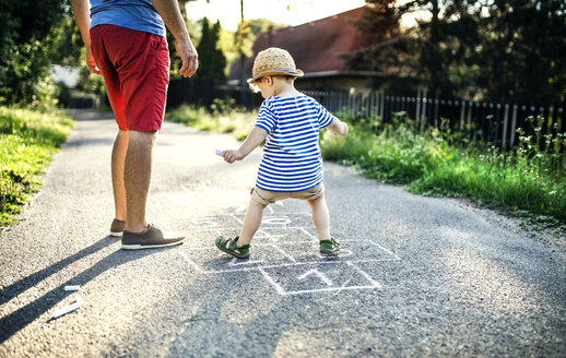 Mature man playing hopscotch together with his little son - HAPF02748