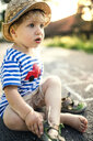 Portrait of toddler boy sitting on the street taking off his shoes - HAPF02751