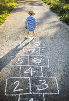 Back view of toddler boy playing Hopscotch - HAPF02754
