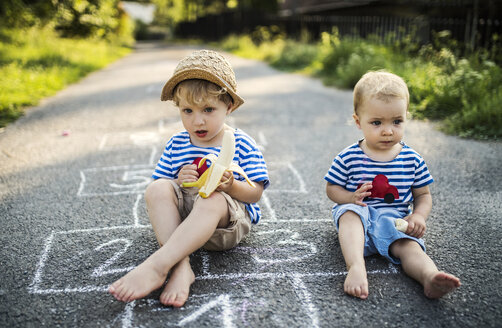 Portrait of toddler boy and his little sister sitting side by side on the street eating bananas - HAPF02760