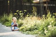 Barefoot baby girl sitting wayside watching something - HAPF02772
