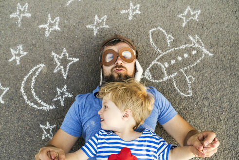 Portrait of mature man wearing pilot hat and his little son lying on asphalt painted with airplane, moon and stars - HAPF02775