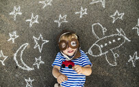 Portrait of smiling toddler wearing pilot hat and goggles lying on asphalt painted with airplane, moon and stars - HAPF02778