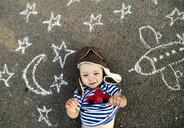 Portrait of smiling baby girl wearing pilot hat lying on asphalt painted with airplane, moon and stars - HAPF02781