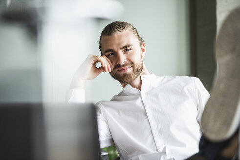 Portrait of smiling businessman sitting in office with feet up - UUF15176