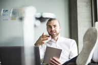 Young businessman sitting in office with feet up holding tablet and talking - UUF15179