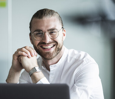 Portrait of smiling young businessman in office - UUF15182