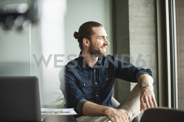 Smiling businessman sitting in office looking out of window - UUF15188 - Uwe Umstätter/Westend61