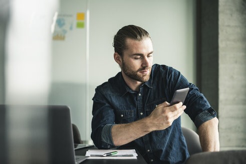 Young businessman sitting in office using cell phone - UUF15200