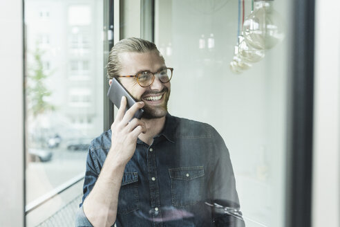 Smiling young businessman on cell phone in office at the window - UUF15218