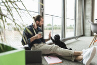 Young businessman with laptop sitting on the floor in office playing with dog - UUF15221