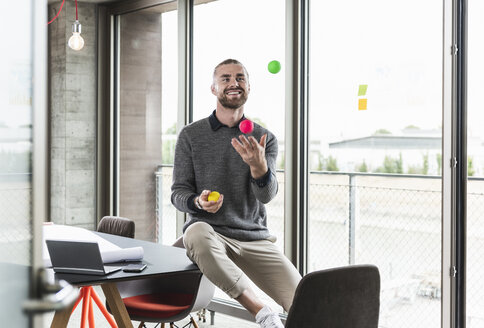 Smiling young businessman sitting at the window juggling with balls - UUF15245