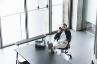 Casual businessman sitting in office with feet up using cell phone - UUF15275
