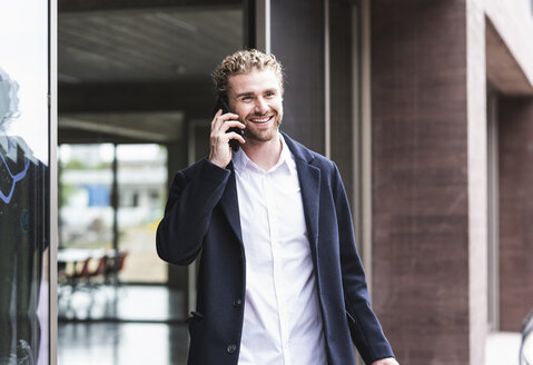 Smiling young businessman on cell phone outside office building - UUF15287