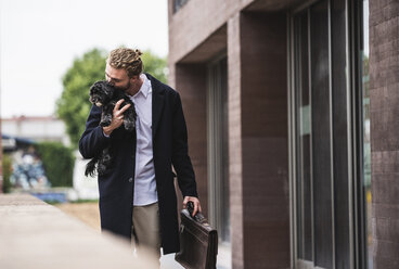 Young businessman cuddling dog outside office building - UUF15290