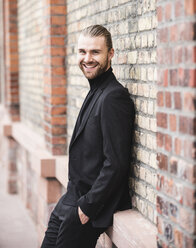 Portrait of smiling fashionable young man leaning against brick wall - UUF15293