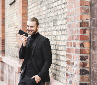 Smiling fashionable young man standing at brick wall using cell phone - UUF15296