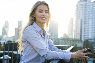 Blonde smiling business woman leaning onto handrail holding smartphone on city rooftop - SBOF01508