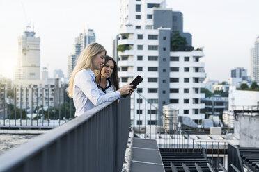 Two businesswomen talking on city rooftop, using digital tablet - SBOF01511