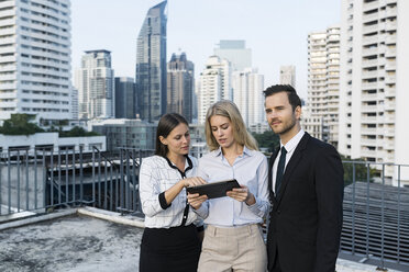 Colleagues with tablet on city rooftop - SBOF01514
