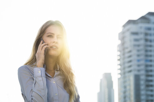 Business woman speaking into smartphone on city rooftop - SBOF01523