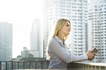 Portrait of blonde business woman leaning onto handrail on city rooftop - SBOF01526