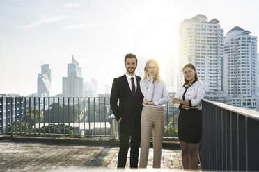 Portrait of two businesswomen and a businessman on rooftop - SBOF01529