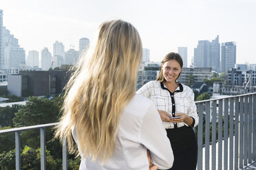 Two female colleagues speaking with each other on city rooftop - SBOF01532