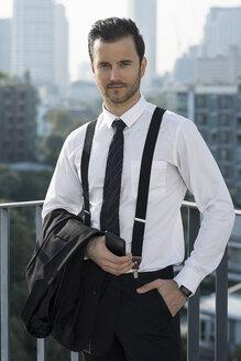 Portrait of business man on city rooftop - SBOF01535