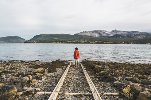 Northern Norway, Man standing alone at fjord, looking at view - KKAF02029