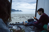 Norway, Lapland, Young people camping in a tent on a beach at fjord - KKAF02071