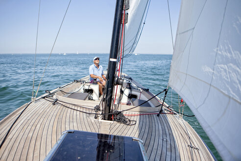 Onboard view from the bow of a  man helming a small sailing yacht, Arcachon Bay, France. - AURF07266
