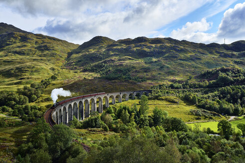UK, Scotland, Highlands, Glenfinnan viaduct with a steam train passing over it - RUEF01997