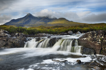 United Kingdom, Scotland, Scottish Highlands, Isle Of Skye, Waterfall at Sligachan river with view to the Cuillin mountains - RUEF02006
