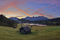 Germany, Bavaria, Werdenfelser Land, lake Geroldsee with hay barn at sunset, in background the Karwendel mountains at sunrise - RUEF02009