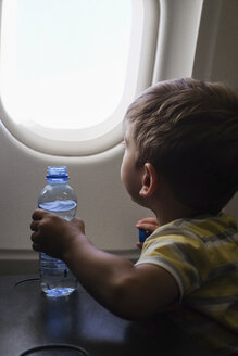 Little boy in an airplane looking out of window - MOMF00506