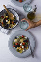 Woman serving mediterranean orecchiette with tomato, olives and mozzarella, water glass - GIOF04544