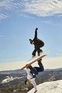 Snowboarder jumping over another doing handplant trick, Vermont, USA - AURF07442