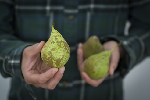 Man's hand holding pear, close-up - JUNF01297