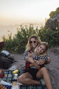 Switzerland, Grosser Mythen, two happy girlfriends on a hiking trip having a picnic break at sunrise - LHPF00041