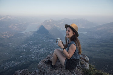 Switzerland, Grosser Mythen, happy young woman on a hiking trip sitting on a rock with a cup - LHPF00044