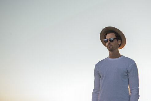 Portrait of young man wearing hat and sunglasses at sunrise - LHPF00047