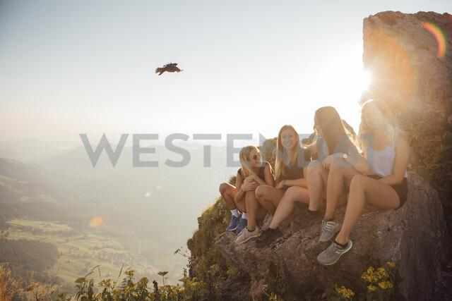 Switzerland, Grosser Mythen, four happy girlfriends on a hiking trip having a break at sunrise - LHPF00056