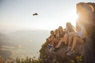 Switzerland, Grosser Mythen, four happy girlfriends on a hiking trip having a break at sunrise - LHPF00056