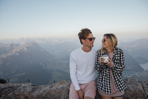 Switzerland, Grosser Mythen, happy young couple on a hiking trip having a break at sunrise - LHPF00062