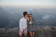 Switzerland, Grosser Mythen, happy young couple on a hiking trip having a break at sunrise - LHPF00065